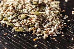 被混合的干燥种子南瓜,芝麻,向日葵,健康吃的胡麻在木黑桌上 免版税库存照片