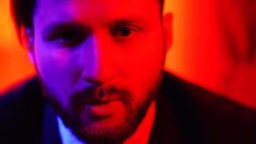 被混淆的困惑的英俊的有胡子的人身分和看照相机被隔绝在明亮的红灯背景 股票录像