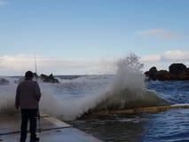 被淹没的海波浪和渔夫 免版税库存照片