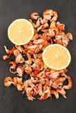 被清洗的和煮熟的小龙虾尾巴用在板岩的柠檬 免版税库存图片