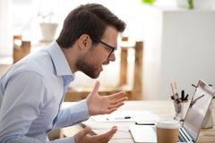 被激怒的企业人坐的工作在办公室 免版税图库摄影