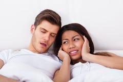 被激怒的妇女覆盖物耳朵,当打鼾在床上时的人 免版税库存照片
