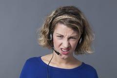 被激怒的年轻callcenter辅助沮丧由在她的耳机的困难的电话 免版税图库摄影