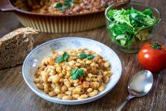 被炖的和被烘烤的白豆用在一块板材和莴苣和蕃茄沙拉的香料用家制面包 免版税图库摄影