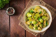 被炖的布鲁塞尔圆白菜发芽,苹果和韭葱在碗 免版税图库摄影
