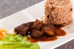 被炖的猪肉服务用米,并且豌豆、莴苣和家做了菜沙拉 库存照片