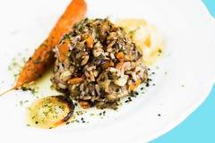 被炖的米用烤蘑菇、红萝卜和葱 图库摄影