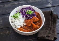 被炖的肉用米和红叶卷心菜在一个白色碗在黑暗的木背景 库存照片