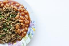 被炖的蘑菇用在西红柿酱的白豆在碗 免版税图库摄影