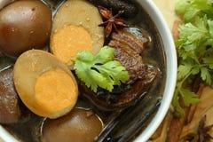 被炖的鸡蛋和猪肉棕色沙司在白色碗 库存照片