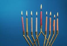 被点燃在menorah的光明节蜡烛在蓝色背景