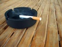 被点燃的烟灰缸香烟 免版税库存图片
