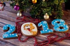 被点燃的背景电灯泡色的装饰诗歌选节假日光 在形状2, 0, 1, 8个数字的蜂蜜曲奇饼,担任主角放置在木背景 免版税库存图片