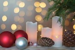 被点燃的蜡烛、锥体和欢乐球在一本圣诞树和诗歌选旁边在背景中 库存照片