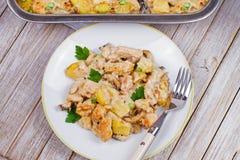 被烘烤的乳脂状的鸡、土豆和蘑菇 图库摄影