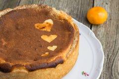 被烘烤的乳酪蛋糕洒与与心脏的可可粉在蛋糕塑造 免版税库存照片