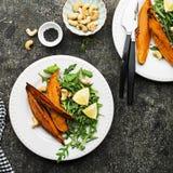 被烘烤的切片一顿素食健康快餐的白薯与沙拉,酸奶调味汁,供食的黑芝麻吃午餐 库存图片