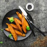 被烘烤的切片一顿素食健康快餐的白薯与沙拉,酸奶调味汁,供食的黑芝麻吃午餐 免版税库存照片