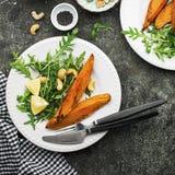 被烘烤的切片一顿素食健康快餐的白薯与沙拉,酸奶调味汁,供食的黑芝麻吃午餐 免版税库存图片