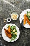被烘烤的切片一顿素食健康快餐的白薯与沙拉,酸奶调味汁,供食的黑芝麻吃午餐 库存照片