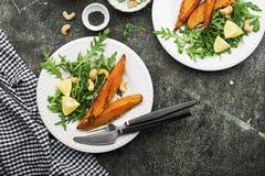 被烘烤的切片一顿素食健康快餐的白薯与沙拉,酸奶调味汁,供食的黑芝麻吃午餐 图库摄影