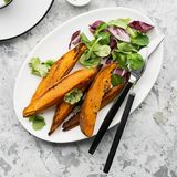 被烘烤的切片一顿素食健康快餐的白薯与沙拉,酸奶调味汁,供食的黑芝麻吃午餐 免版税图库摄影
