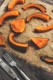 被烘烤的切片在羊皮纸的南瓜与叉子和刀子 与温暖的树荫的被定调子的照片 选择聚焦 库存照片