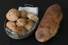 被烘烤的发酵母家制面包和小圆面包与种子-土气质量 在与餐巾的老古色古香的金属篮子的小圆面包 豆杆 免版税库存图片
