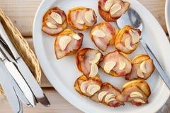 被烘烤的土豆一半用烟肉和大蒜在板材 免版税库存照片