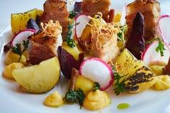 被烘烤的土豆切片和甜菜与菜和烤肉烟肉关闭 免版税库存照片