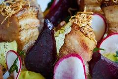 被烘烤的土豆切片和甜菜与菜和烤肉烟肉关闭 免版税图库摄影