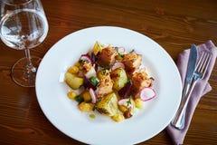 被烘烤的土豆切片和甜菜用菜和烤肉烟肉在黑暗的木桌上在餐馆内部服务 库存照片