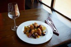 被烘烤的土豆切片和甜菜用菜和烤肉烟肉在黑暗的木桌上在餐馆内部服务 库存图片