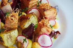 被烘烤的土豆切片和甜菜用菜和烤肉烟肉 免版税库存照片
