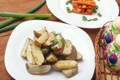 被烘烤的土豆和红萝卜用葱在一块白色板材 免版税库存图片