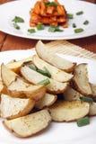 被烘烤的土豆和红萝卜用葱在一块白色板材 库存照片