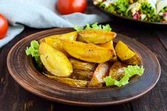 被烘烤的土豆在家在木桌上的黏土碗 库存图片