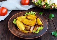 被烘烤的土豆在家在木桌上的黏土碗 免版税库存图片