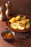 被烘烤的土豆在棕色土气桌的板材楔住 免版税库存照片