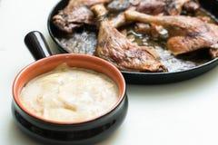 被烘烤的土豆用乳酪和烤鸭子腿 库存照片