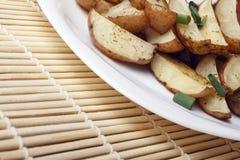 被烘烤的土豆用在一块白色板材的葱 免版税库存照片