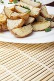 被烘烤的土豆用在一块白色板材的葱 库存图片