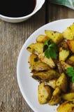 被烘烤的土豆用在一块白色板材的调味汁 免版税库存图片