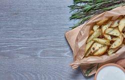被烘烤的土豆用在灰色背景的迷迭香 库存图片