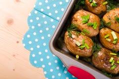 被烘烤的土豆用在盘子的葱 免版税库存图片