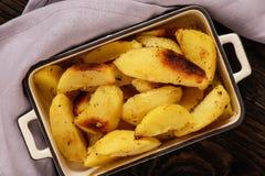 被烘烤的土豆用大蒜和香料在木背景 免版税图库摄影