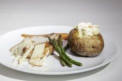 被烘烤的土豆用猪腰和切细的苹果 免版税库存图片