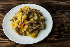 被烘烤的土豆用肉、红萝卜和葱 免版税库存图片