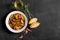 被烘烤的土豆用迷迭香和大蒜 图库摄影
