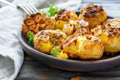被烘烤的土豆用香料、橄榄油和大蒜 免版税库存照片